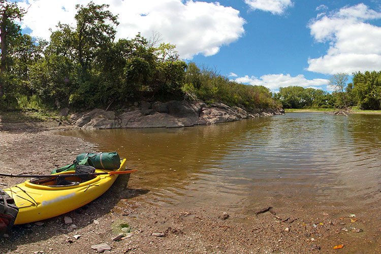 Photo of a yellow kayak moored on the shore of the river.