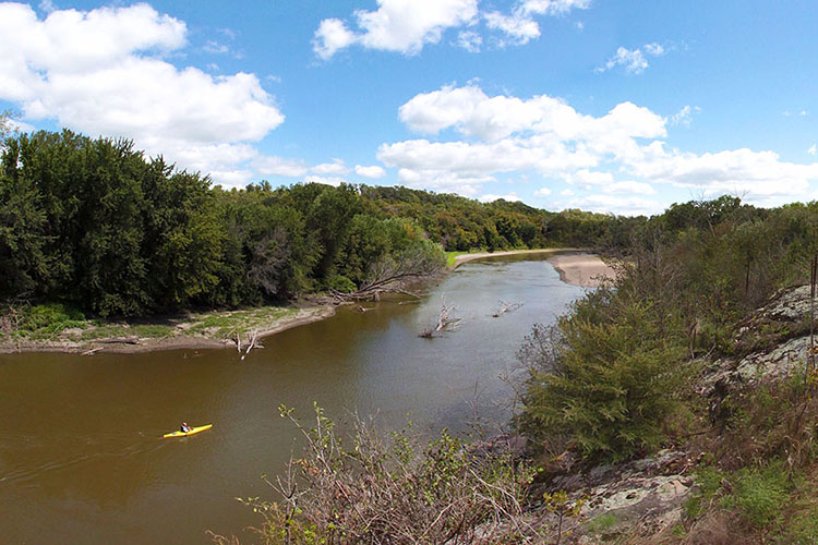 Photo of a yellow kayak floating on river as water curves around a bend.
