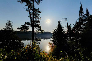 Photo of a bright full moon rising above Coon Lake at Scenic State Park.
