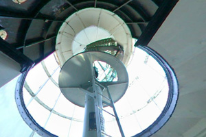 Photo of aFresnel lens and beacon at the top of a winding staircase inside the lighthouse.