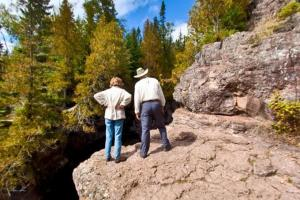 Photo of visitors looking at the deep, narrow gorge cut by the Temperance River.