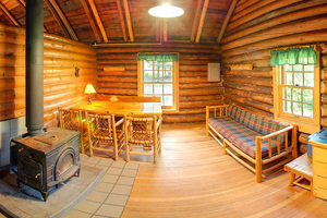 Photo of a rustic two-room cabin interior, that sleeps six, comes with a canoe, and is available year-round.