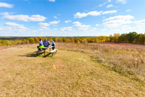 Photo of a family at a picnic table in the prairie overlook.