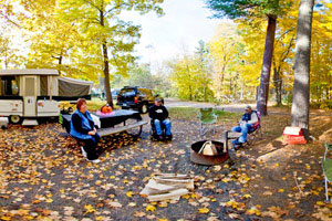 Photo of a family relaxing near their camper in one of William O'Brien State Park's campsites.