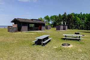 Photo of picnic tables, fire rings, and a shelter near the beach.