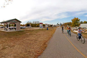 Photo of a bicyclists traveling along as trail passes Lake Christina, just to the north of Melby, Minnesota.