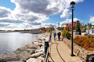 Photo of walkers enjoying the shoreline path in Grand Marais on a fall day under the blue sky.