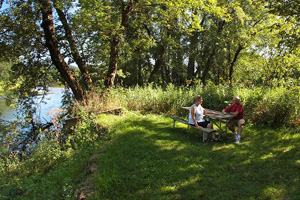 Photo of the trail visitors enjoying a picnic along the banks of the Root River.