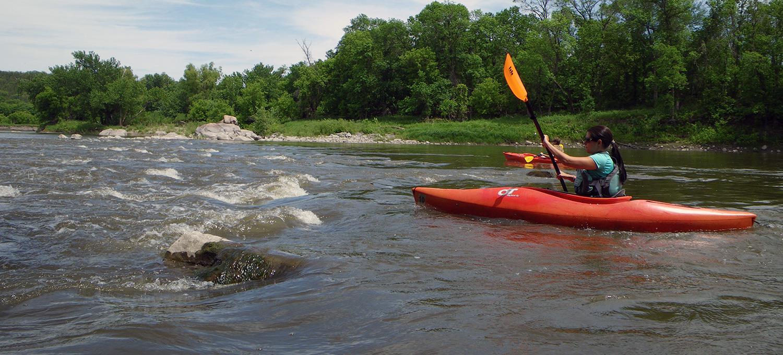 kayakers paddle through riffles