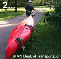 Photo of bicyclist with a canoe on a cart behind his bike
