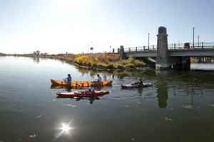 Photo of the paddlers journeying under a bridge between Lake Irving and Lake Bemidji.