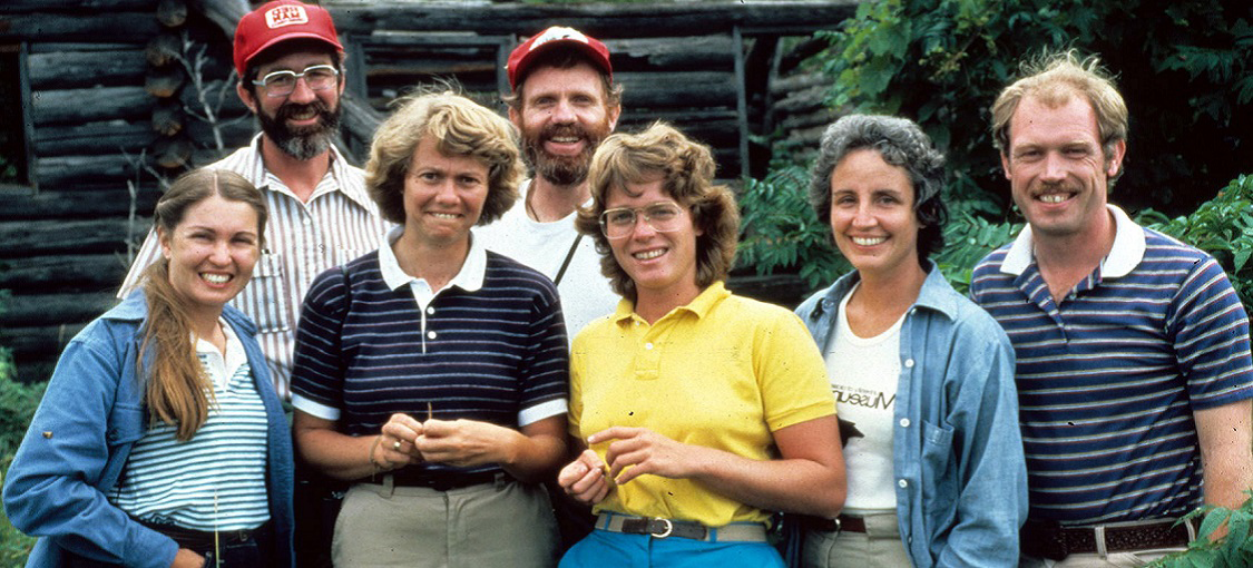 Seven people standing in line smiling at the camera