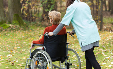 care giver walking with patient in wheel chair