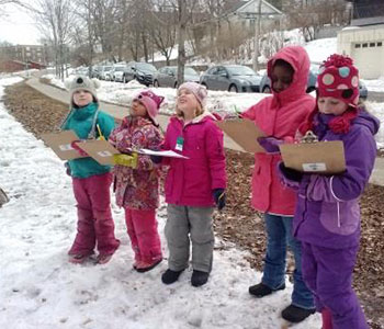 student outside in the winter writing on clip boards