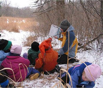 teacher reading to students outside in the winter