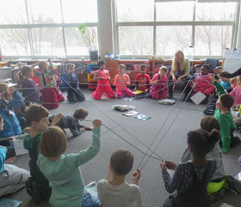 students in a classroom with yard across the room like a web.