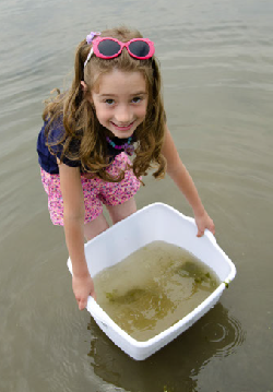 girl with tub of lake water