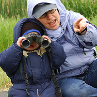 A mother and child. The child is holding binoculars to their face.