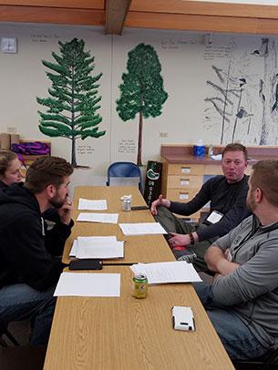 four teachers sitting around a table talking
