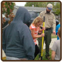 students planting tree with forester