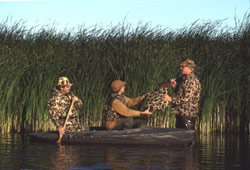 Three duck hunters wearing proper life jackets