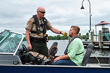 man getting his blood alcohol limit tested by a Conservation Officer on a boat