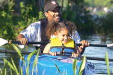father and daughter kayaking together wearing life vests