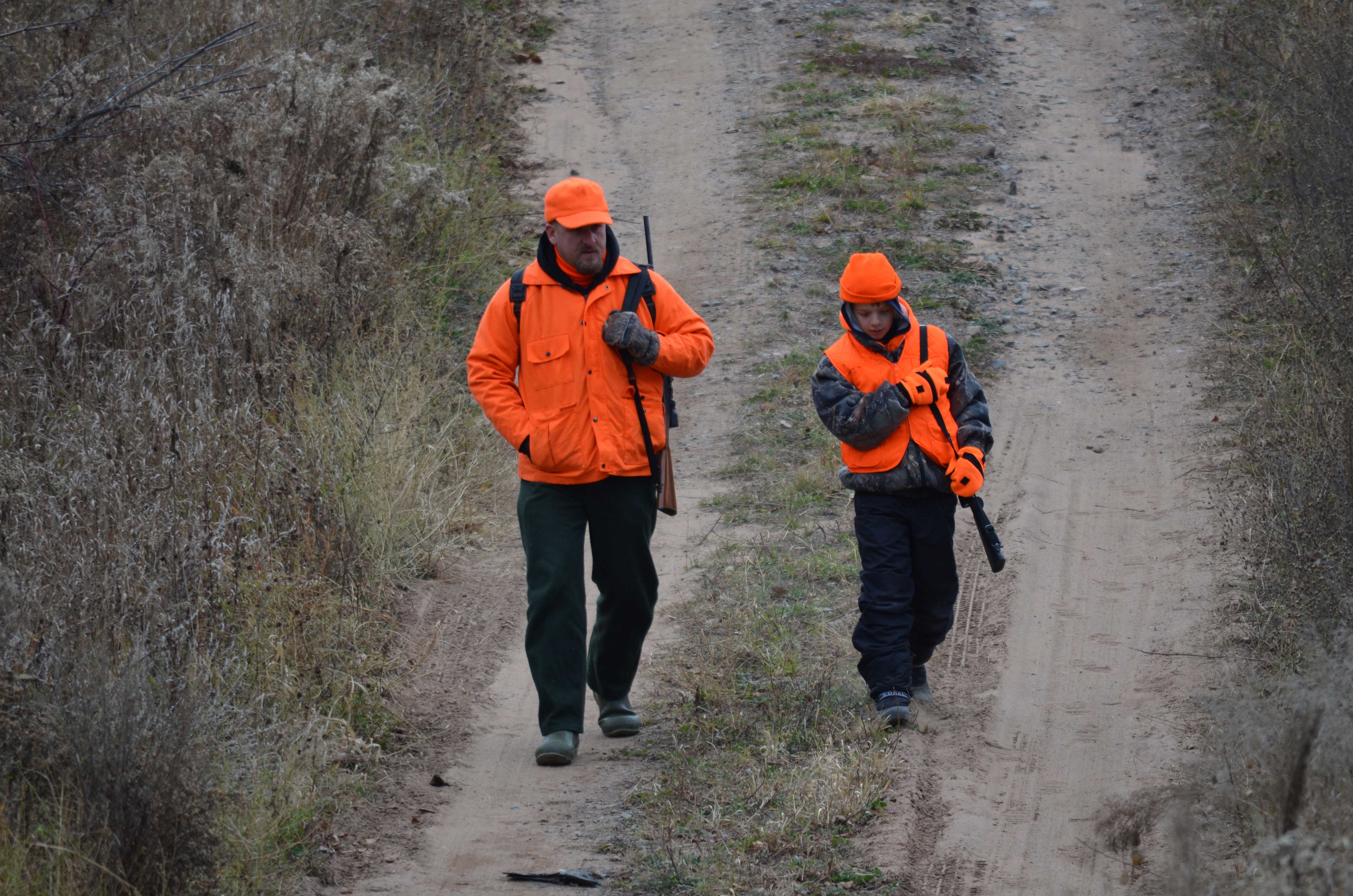 An adult and youth in blaze orange walk next to each other on a hunt.