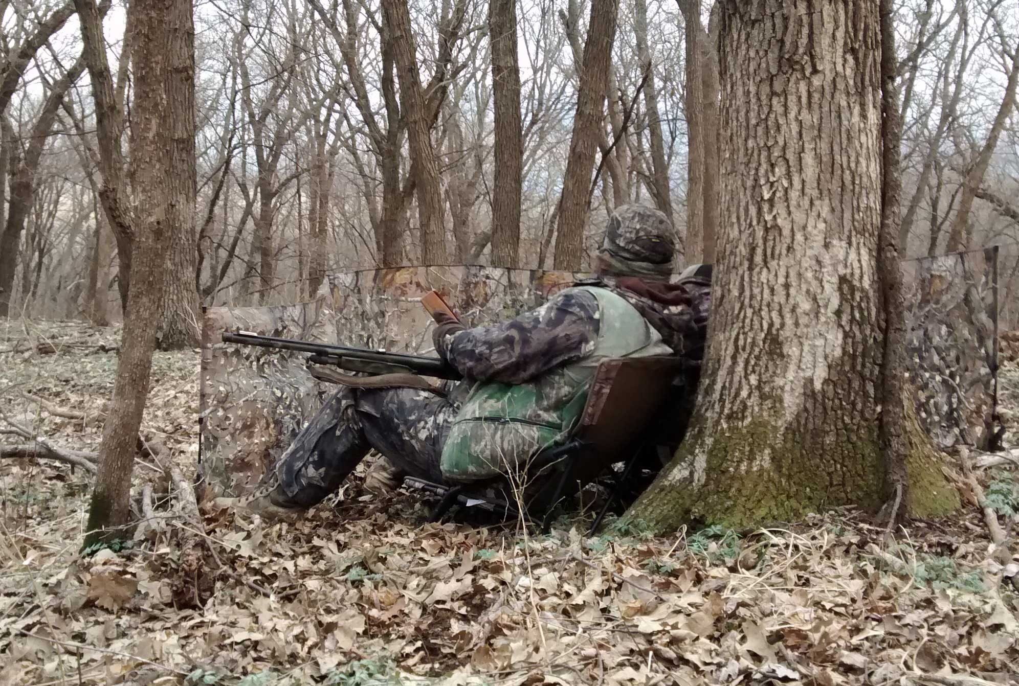 a turkey hunter sitting against a tree in the spring