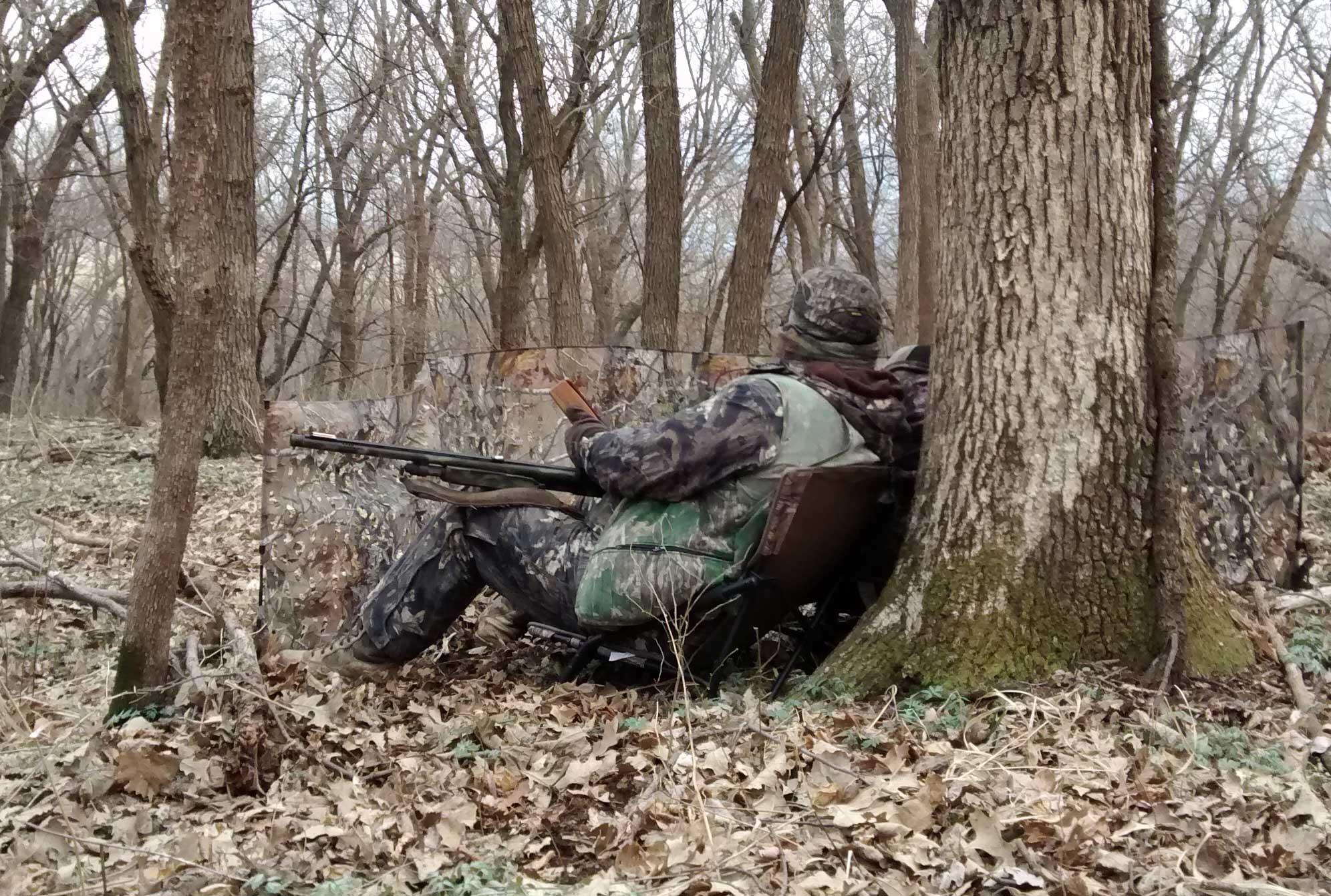 a turkey hunter against a tree