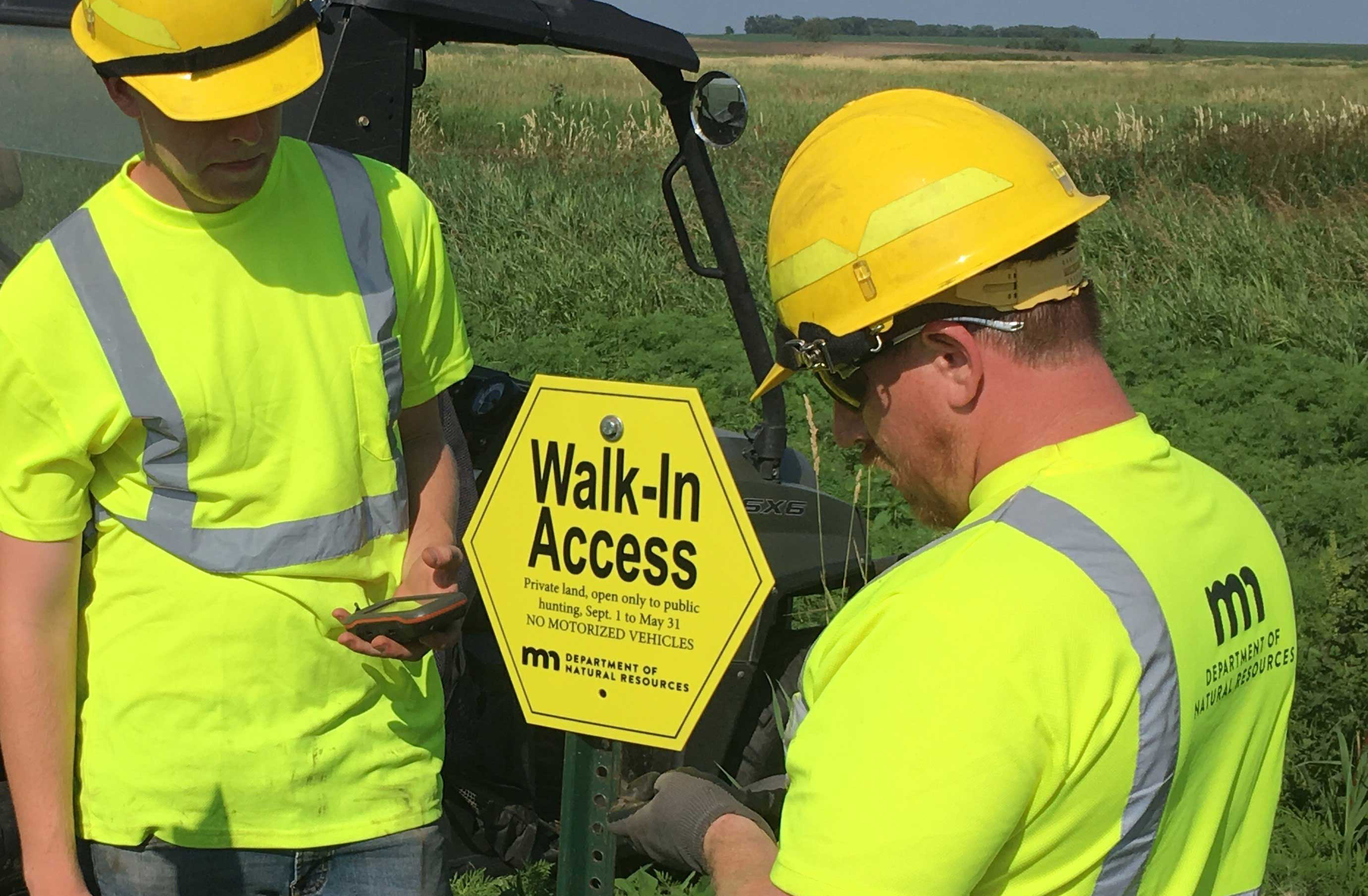 DNR staff place a Walk-In Access sign.