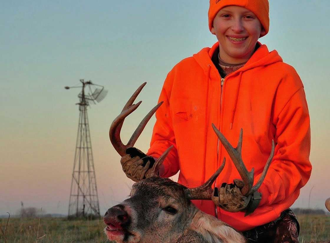 A youth poses with a buck he harvested during the youth deer season