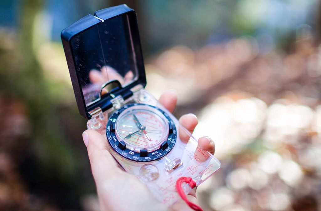 A hand holding a compass to get bearings.