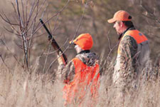 An adult helps a youth on his first pheasant hunt