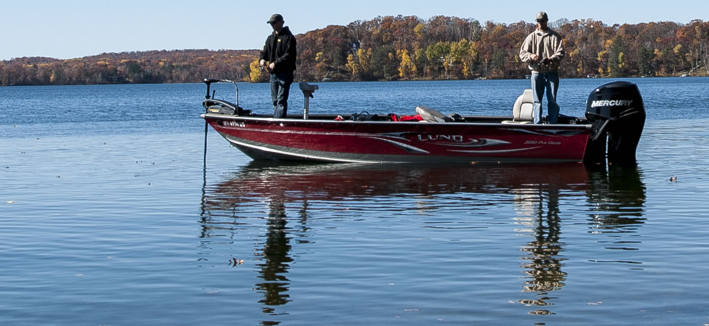 Anglers fishing from a boat in fall on a Minnesota lake.