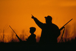 Young and old hunters shilloutted on a hill