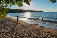 People splashing in the water on a beach at Mille Lacs Lake.
