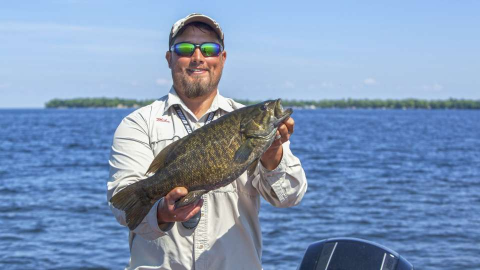 Angler in boat holding large smallmouth bass caught in Mille Lacs Lake