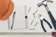 Notebook, hardhat, tools, nails and tape measure