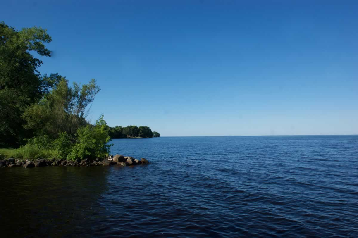 Photo from the shore of Mille Lacs Lake showing blue water underneath a clear blue sky and green trees on the shoreline