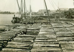 photo: Row upon row of logs await loading at a shipyard.