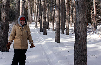 Peggy Meseroll standing in snow covered trail by tall pine trees.