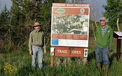 Bill Bailey and Tim Gossman standing next to a Ninebark Road Trailhead sign