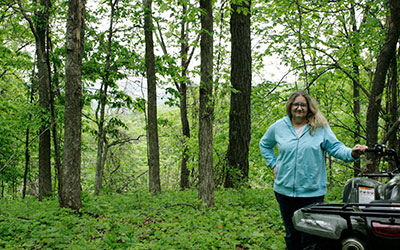 Janice Stalsberg standing by an ATV in a forest.