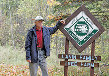 Patrick Lanin stading by Tree Farm sign