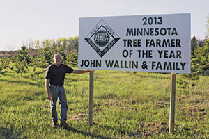 John Wallin standing by Tree Farmer sign