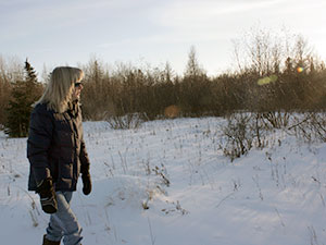 Patricia Lenoch walking in a snow covered field.