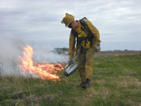 Lighting a prescribed fire on a prairie.