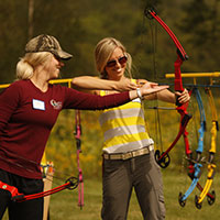 An instructor teaches a woman how to use a bow.