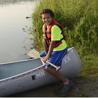 child wearing lifejacket ready to get in a canoe